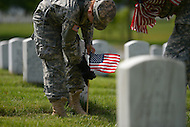 May 23, 2013  (Arlington, Virginia)  Staff Sgts. Brooke Stevens (left) and Kevin Lynch, of the 3rd U.S. Infantry Regiment (the Old Guard), places an American flag before a gravestone at Arlington National Cemetery. The annual tradition, known as Flags In, honors every fallen soldier's grave with a flag.  (Photo by Don Baxter/Media Images International)