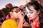 "Oct. 30, 2009 -- PHOENIX, AZ: MICHAEL GARCIA helps THANIA BETANCOURT put on her makeup before the Zombie Walk in Phoenix Friday. About 200 people participated in the first ""Zombie Walk"" in Phoenix, AZ, Friday night. The Zombies walked through downtown Phoenix ""attacking"" willing victims and mixing with folks going to the theatre and downtown sports venues.  Photo by Jack Kurtz"