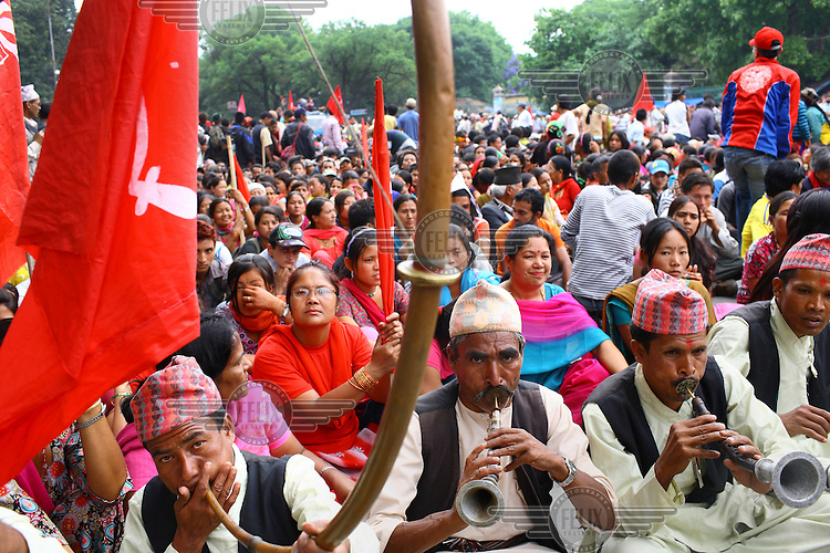 People sit down and play instruments in protest at a strike called by the Unified Communist Party of Nepal (UCPN) to remove the ruling government. The Maoist opposition blocked streets leading to key government offices on the 6th May, the fifth day of their crippling general strike to demand the prime minister's resignation, but the government has vowed not to bow to the protesters' pressure. The Maoists, known to use violence to back their strike calls, have demanded that residents halt all travel and keep businesses and schools closed since Sunday in their campaign to get Prime Minister Madhav Kumar Nepal to resign and hand power to a Maoist-led government. The strike has shut down most businesses, schools and transport, with daily activity grinding to a standstill.