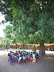 Children in class under a tree in a primary school in Bunj, South Sudan, sponsored by Jesuit Relief Service. The community is host to more than 130,000 refugees from the Blue Nile region of Sudan. JRS, with support from Misean Cara, provides educational and psycho-social services to both refugees and the host community.