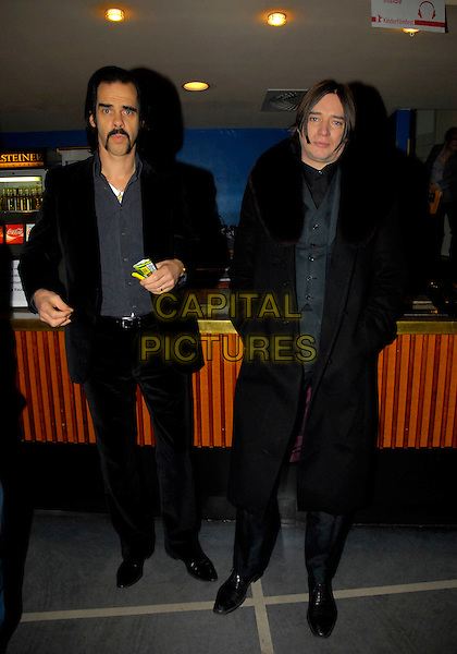 "NICK CAVE & GUEST.Press conference for ""The Proposition"" at the 56th Berlin (Berlinale) Film Festival, Berlin, Germany..February 13th, 2006.Ref: KRA.full length black jacket suit rolling tabacco grey gray suit.www.capitalpictures.com.sales@capitalpictures.com.©Capital Pictures"