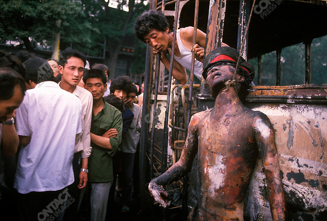 The body of a dead soldier, who was lynched and burned, near the Communist Party headquarters. Beijing, China, June 4, 1989