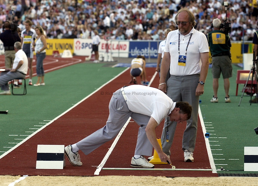 Photo. Henry Browne..Norwich Union London Grand Prix Athletics at Crystal Palace. 30/07/2004..Womens Long Jump..Athletics officials marking out the jumps line.