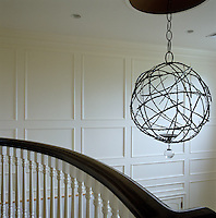 A bronze chandelier by Herve van der Straten hangs above the staircase