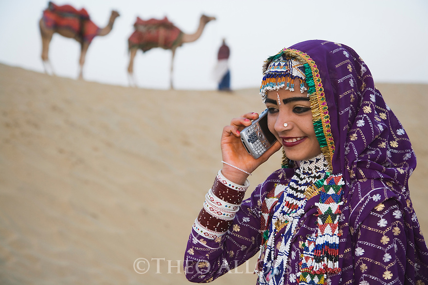 Rajasthani dancer in traditional costume talking on cell phone in the Thar Desert;.Camel driver with camels in background; Rajasthan, India --- Model Released
