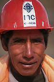 Sachsayhuaman, Cusco, Peru. Quechua man wearing a red hard hat of INC, the Peruvian National Archaeology Institute.