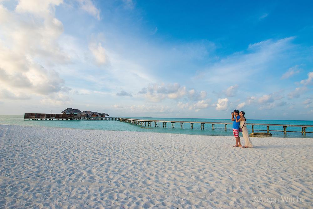 Maldives, Rangali Island. Conrad Hilton Resort. Couple at the beach watching the sunset.