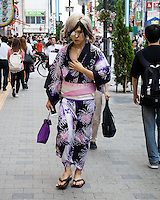 A male host dressed in a female yukata, a summer kimono. There were many other hosts dressed similarly on that day in Shinjuku. Most likely they were heading to a birthday party in one of the clubs that required all males to come dressed in female yakatas.