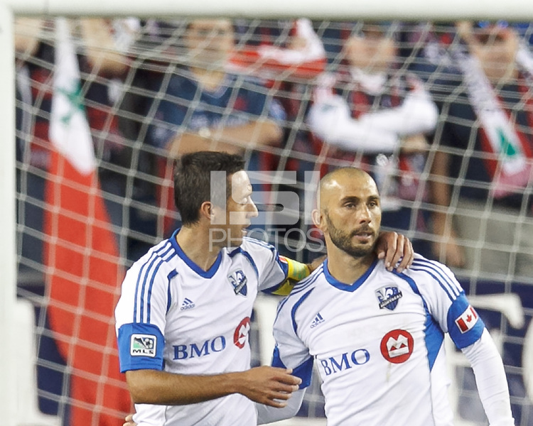 Montreal Impact forward Marco Di Vaio (9) celebrates his goal with Montreal Impact midfielder Davy Arnaud (22). In a Major League Soccer (MLS) match, Montreal Impact (white/blue) defeated the New England Revolution (dark blue), 4-2, at Gillette Stadium on September 8, 2013.