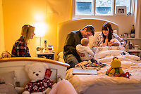 A woman breastfeeding one of her 5 month old twins on her bed in her bedroom.  Her husband is sitting next to her with the other twin on his lap with the twins' grandmother looking on.<br /> <br /> Image from the &quot;We Do It In Public&quot; documentary photography project collection: <br />  www.breastfeedinginpublic.co.uk<br /> <br /> Hampshire, England, UK<br /> 11/02/2013