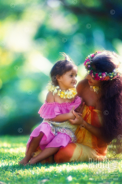 A beautiful Polynesian woman with her small daughter both dressed in colorful Hawaiian clothes and wearing plumeria leis, share a quiet moment on the grass.