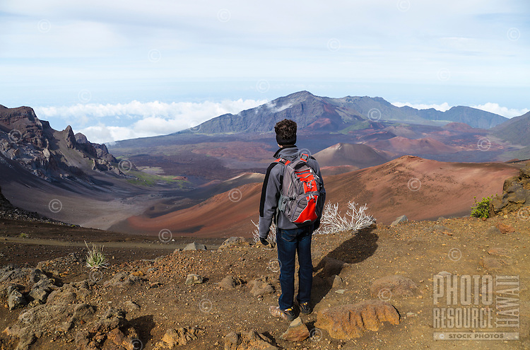 A hiker takes in the view along the Sliding Sands Trail, Haleakala National Park, Maui.