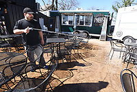 LUNCH BUNCH<br />David Porras (cq) hoses down tables on Wednesday March 26 2020 at an outdoor dining area near Lawrence Plaza in downtown Bentonville. Porras was sprucing up the area in preparation for lunch customers. Go to nwaonline.com/200326Daily/ to see more photos.<br />(NWA Democrat-Gazette/Flip Putthoff)