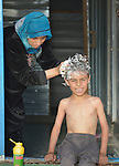Jehan Hamza washes her son Ali's hair in the Zaatari refugee camp near Mafraq, Jordan. The boy benefits from an anti-lice campaign sponsored by International Orthodox Christian Charities, a member of the ACT Alliance.<br /> <br /> Established in 2012 as Syrian refugees poured across the border, the Zaatari camp held more than 80,000 refugees by 2015, and was rapidly evolving into a permanent settlement. ACT Alliance member agencies provide a variety of services to refugees living in the camp.