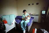 A young mother with her baby in a hostel for homeless families run by Haringey Council in North London.