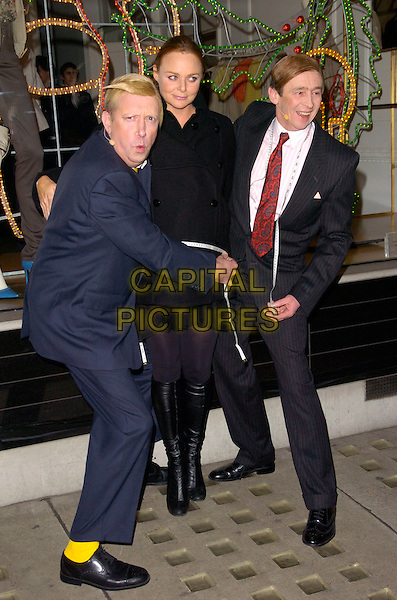 MARK WILLIAMS, STELLA McCARTNEY & PAUL WHITEHOUSE.Stella McCartney Store - Christmas lights switch on, Stella McCartney, London, England. .November 29th, 2007 .full length the fast shoe blue suit grey gray pinstripe pleated skirt boots tights yellow socks funny hug embrace.CAP/CAN.©Can Nguyen/Capital Pictures