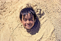 Young local boy is buried in sand up to his neck.