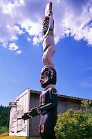 Kwakwaka'wakw (Kwakiutl) Totem Pole at U'mista Cultural Centre, Alert Bay, Cormorant Island, BC, British Columbia, Canada - Man holding Copper stands atop Dzoonokwa (Wild Woman of Woods)
