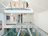 A glass bridge crosses the triple height atrium at the centre of the remodelled Victorian house. Glass walls throughout allow light to circulate through the open space from the skylight