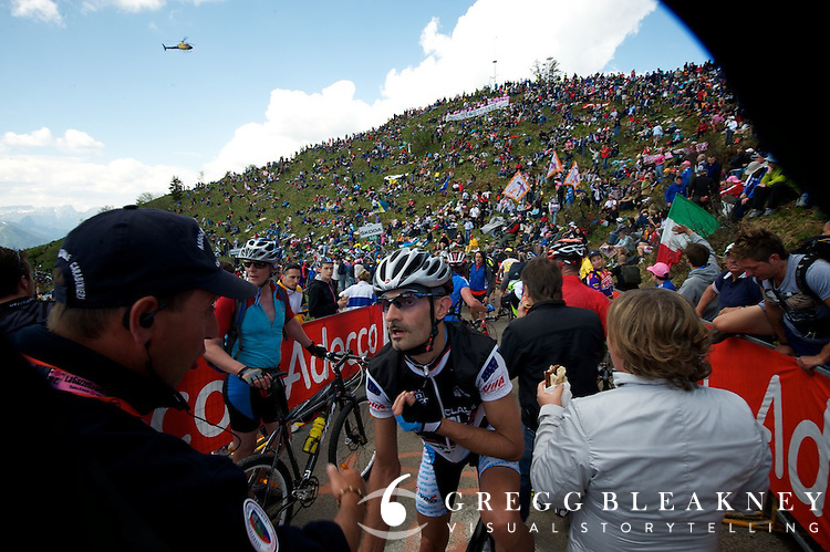 An Italian enthusiast rider argues with race officials, who'd shut down the Zoncolan climb at only 100 meters from the top to prepare for police and Giro offical cars to pass.  He did not make it to the top today.