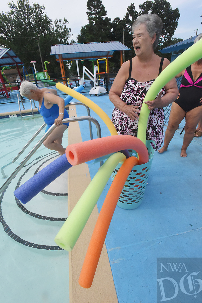 NWA Democrat-Gazette/FLIP PUTTHOFF <br /> POOL PARTY<br /> Frances Croxdale (right) hands out swimming noodles on Wednesday Aug. 8 2019 during a water aerobics class at the Gravette city pool. The Billy V. Hall Senior Activity and Wellness Center in Gravette has offered water aerobics through the summer. The final session will be Friday. Once Gravette schools start on Aug. 14, the pool will be open Saturdays and Sundays only through Labor Day weekend.