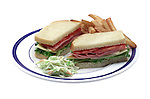 lunch plate with cold cut sandwich and french fries and cole slaw on shadowless white background