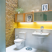 A bathroom with white tiled floor and exposed brick wall