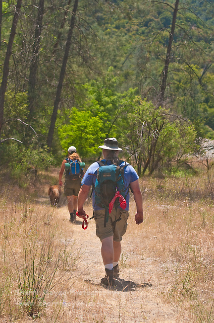 Couple hiking with their dog along the North Fork of the American River, Weimar, California.
