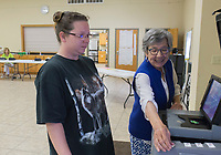 NWA Democrat-Gazette/CHARLIE KAIJO Brenda Taylor (right) helps Brandy Reeder of Garfield (left) enter her ballot during an election, Friday, July 5, 2019 at the NEBCO Community Building in Garfield. <br /> <br /> The Northeast Benton County Fire Department is holding a special election to increase fire dues.