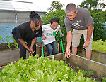 Volunteer Andrew Grull gives a tour of the urban garden to 4-H ambassador Caleb Kinzinger, 16, from Freeburg, Ill and Jackie Joyner Kersee on Thursday, May 30, 2019 in East St. Louis, Ill. (Tim Vizer/AP Images for National 4-H Council)