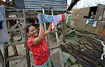 As Victoria Graboso (right) looks on, Corazon Graboso hangs her laundry to dry in Bacubac, a seaside neighborhood in Basey in the Philippines province of Samar that was hit hard by Typhoon Haiyan in November 2013. The storm was known locally as Yolanda. Graboso and her family currently live in the temporary shelter behind her. The ACT Alliance has been providing a variety of assistance to survivors here.