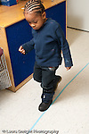 Education preschool 3-4 year olds developmental assessment boy walking along straight line on floor physical development