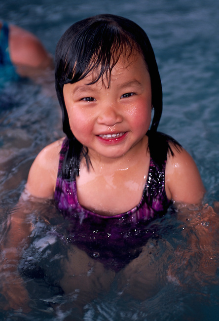 Young Asian girl smiling while in hot tub, Estes Park, CO