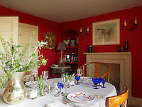 The intimate dining room is painted a warm and vibrant shade of red and furnished with Chinese chairs