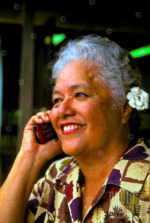 A smiling part-Hawaiian woman makes a call on her cell phone