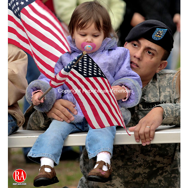 NAUGATUCK, CT- 11 NOVEMBER 2008 --111108JS01-Spec. Nate Flores, of Naugatuck, a member of the Connecticut National Guard, watches the Naugatuck Veterans Day ceremony with his daughter Abigail Flores on the Naugatuck Green on Tuesday. <br /> Jim Shannon / Republican-American