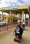 ANDRADE, CA, U.S. -March 19: An American couple in motorized wheelchairs cross the border to visit the Mexican town of Algodones March 19, 2005 from the U.S. The once dusty little town with one dentist in the 1960s has become a mecca for retired Americans in search of less expensive medical services and prescription drugs.©Radhika Chalasani