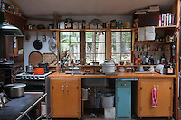 A wall of the kitchen with views out over the clearing is taken up with cupboards on wheels beneath a wooden work surface