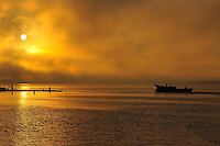 Fisherman boat leaving for new hunt during yellow sunrise
