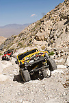 A yellow Jeep with the Motherlode Rock Crawlers travels over a pile of rocks in a road in the Argus Range, Calif.