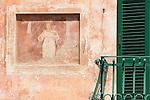 A faded fresco next to an iron green balcony in Griante, a town on Lake Como, Italy.