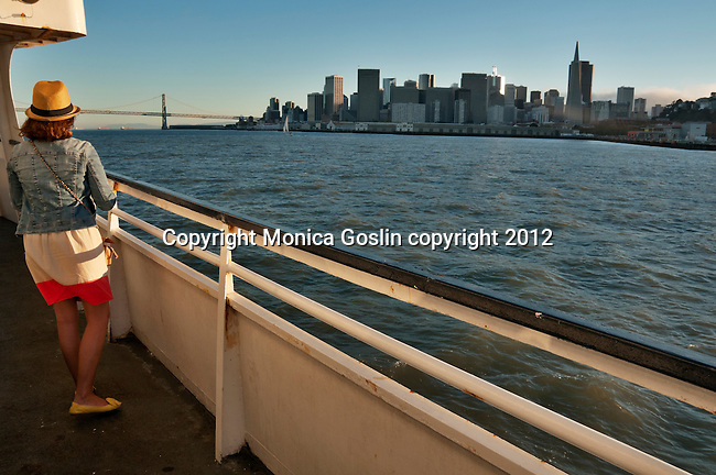 San Francisco, California skyline as seen from a ferry boat with a girl in the foreground with a straw hat and jean jacket