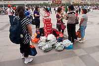 Daytime landscape view of women with bags standing in the square in front of the Zhengzhou Railway Station in the Zhōngyuán Qū of Zhengzhou in Henan province.  © LAN