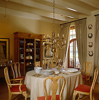 The traditional dining room has a double-tiered brass chandelier as its centrepiece