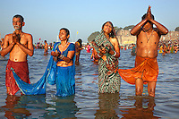 India. Uttar Pradesh state. Allahabad. Maha Kumbh Mela. Two Indian Hindu devotees couples take a holy dip and pray in Sangam. In each couple, the man and the woman are tied to each other as a symbol of unity for ever. Both women wear sarees and both men a Janeu which is a consecrated thread worn by each and every Hindu Brahmin of India. The Kumbh Mela, believed to be the largest religious gathering is held every 12 years on the banks of the 'Sangam'- the confluence of the holy rivers Ganga, Yamuna and the mythical Saraswati. In 2013, it is estimated that nearly 80 million devotees took a bath in the water of the holy river Ganges. The belief is that bathing and taking a holy dip will wash and free one from all the past sins, get salvation and paves the way for Moksha (meaning liberation from the cycle of Life, Death and Rebirth). Bathing in the holy waters of Ganga is believed to be most auspicious at the time of Kumbh Mela, because the water is charged with positive healing effects and enhanced with electromagnetic radiations of the Sun, Moon and Jupiter. The Maha (great) Kumbh Mela, which comes after 12 Purna Kumbh Mela, or 144 years, is always held at Allahabad. Uttar Pradesh (abbreviated U.P.) is a state located in northern India. 9.02.13 © 2013 Didier Ruef