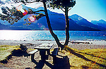 Cameron Bay in Upper Waterton Lake water sky and mountains Alberta Canada with sun lens flare and picnic table