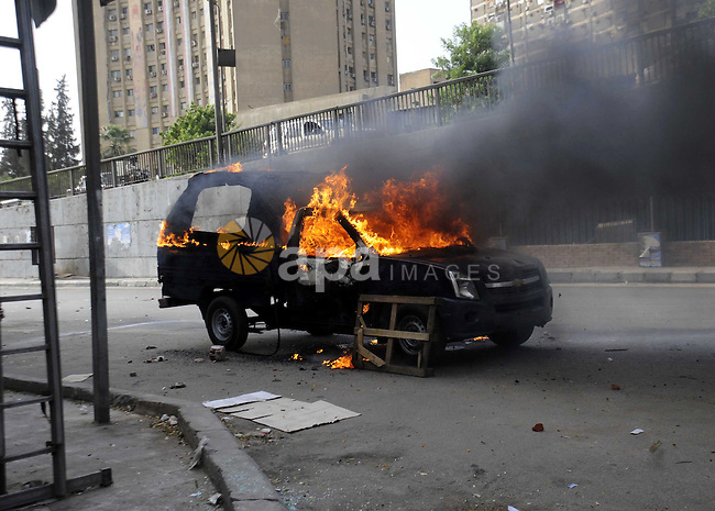 A burning Egyptian police car is seen in front of al-Zamalek football club's headquarters in Cairo on Sept. 19, 2013. Members of a hardcore group of fans of the Zamalek football club, the Ultra White Knights (UWK), stormed the club's headquarters in Cairo on Thursday following a protest demanding changes to the club's leadership. Photo by Ahmed Asad