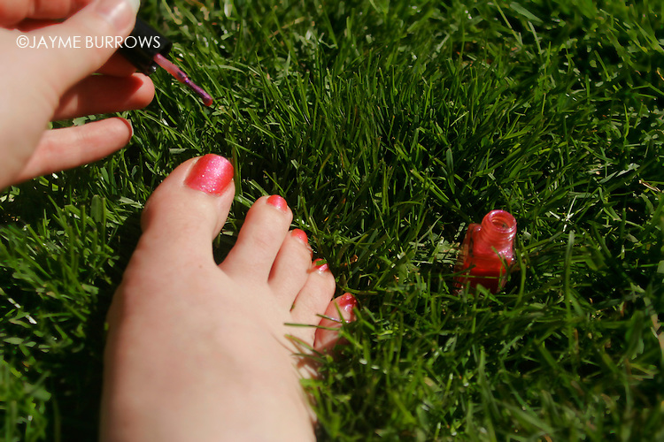Painting toe nails in the grass.