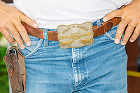 """Farmer Kyle Gilchrist of Douds, Iowa, wears a belt buckle for his ranch, the Star G Ranch, at the Iowa State Fair in Des, Moines, Iowa, on Sun., Aug. 11, 2019. Gilchrist said he didn't vote for Trump in 2016 and instead wrote in Chris Christie's name """"because he believes in small government,"""" Gilchrist said."""