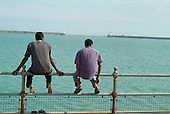 Two refugees from Zaire look out to sea from the promenade near a Dover hotel used by Migrant Helpline to house asylum-seekers awaiting decisions on their asylum applications..